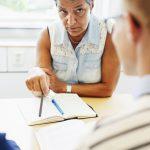mature-professor-teaching-students-at-desk-in-clas-E7WVKKS