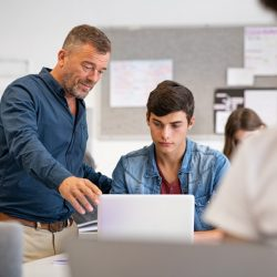 professor-helping-student-during-computer-class-4LD663M